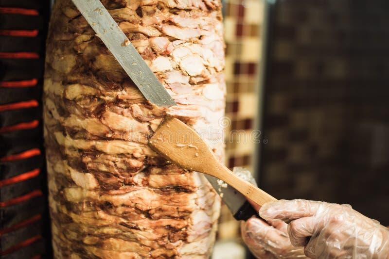 烹调shawarma和ciabatta在咖啡馆 一次性手套裁减肉的一个人在串 库存照片