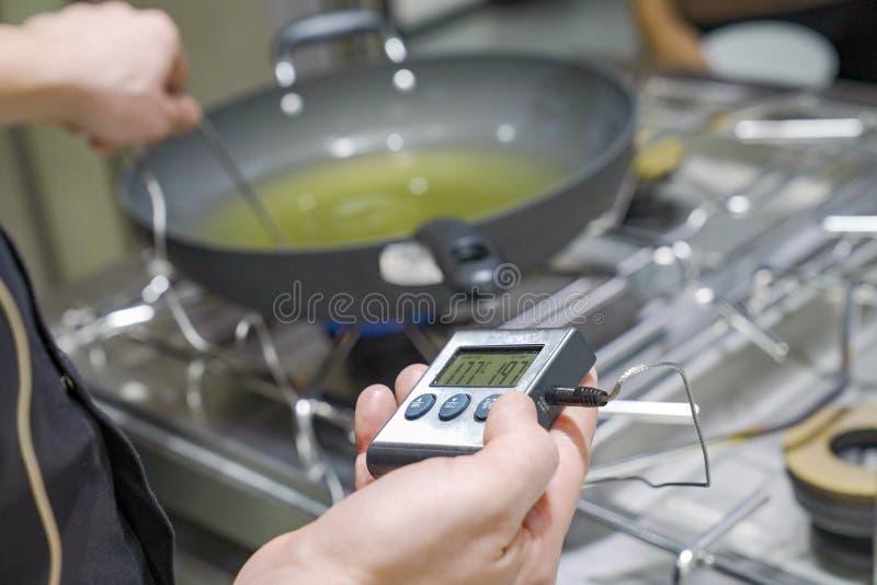 烹调Themometer措施程度油或油煎在平底锅 免版税库存照片