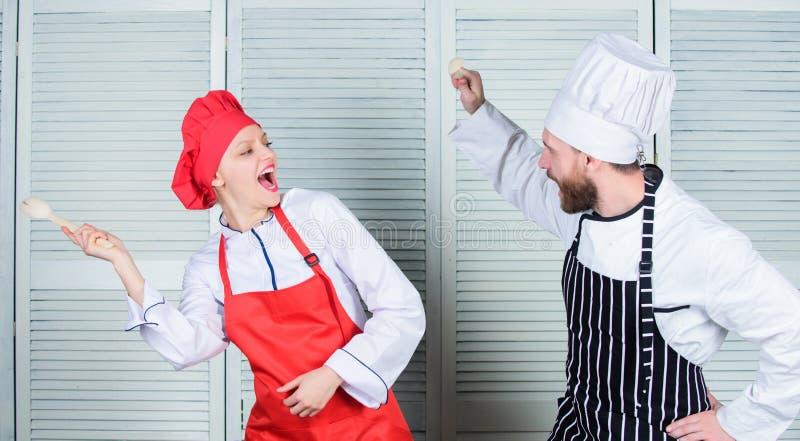 烹饪争斗概念 妇女和有胡子的人烹饪展示竞争者 最后烹调挑战 烹饪争斗  免版税库存图片