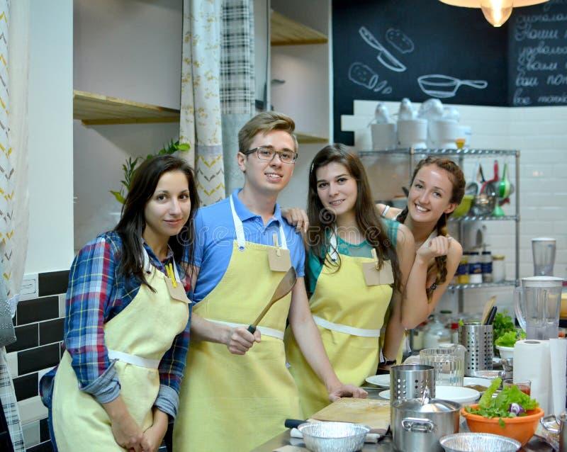 烹饪课 年轻愉快的朋友在厨房里 库存图片
