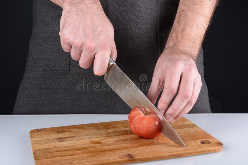 烹饪过程的照片 一个人切与一把快刀的一个蕃茄 库存照片