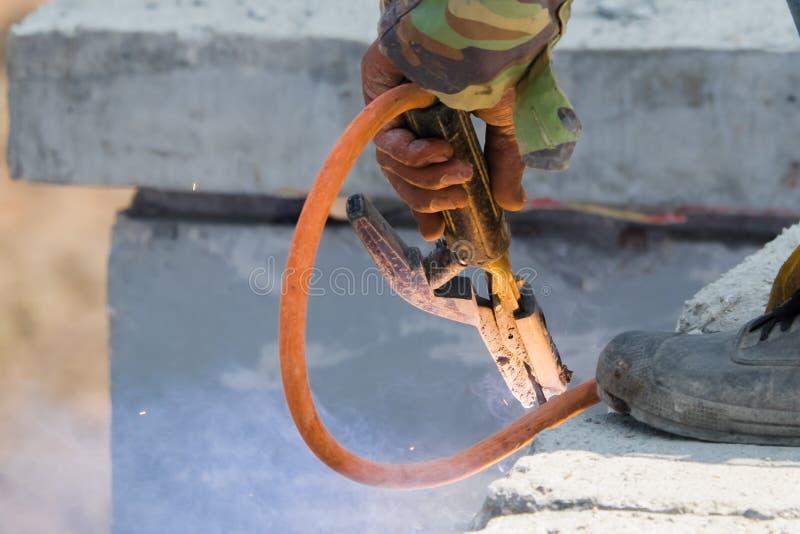 焊工人焊接的铁棍支持预制混凝土墙壁、工作者有无保护的和危险 库存照片