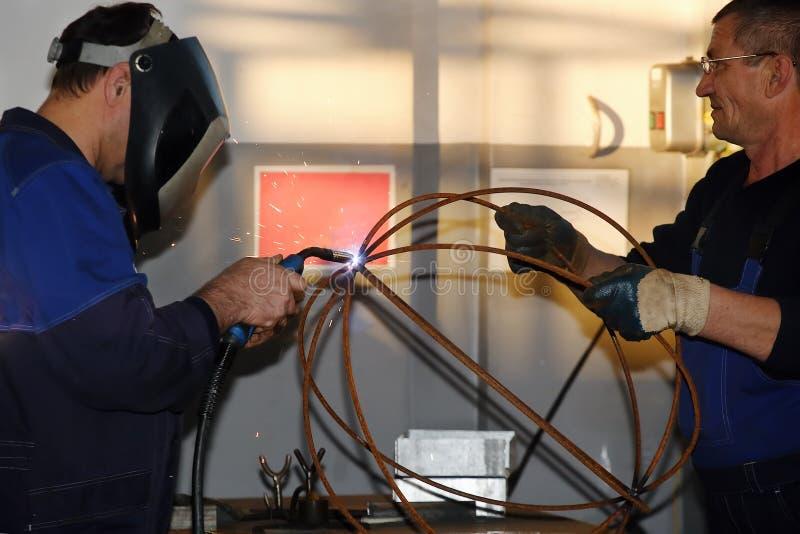 焊工和辅助  两名白人在车间做一个金属制品 免版税库存图片