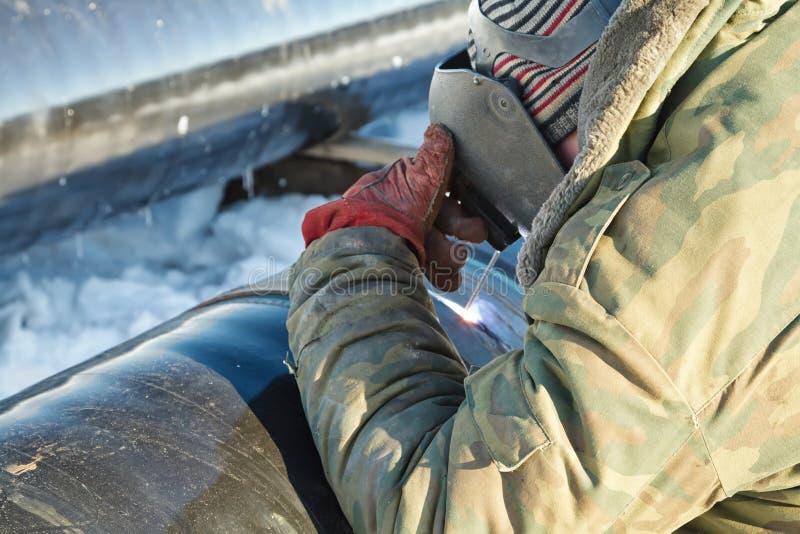 焊工在冬天情况执行焊接管道 库存照片