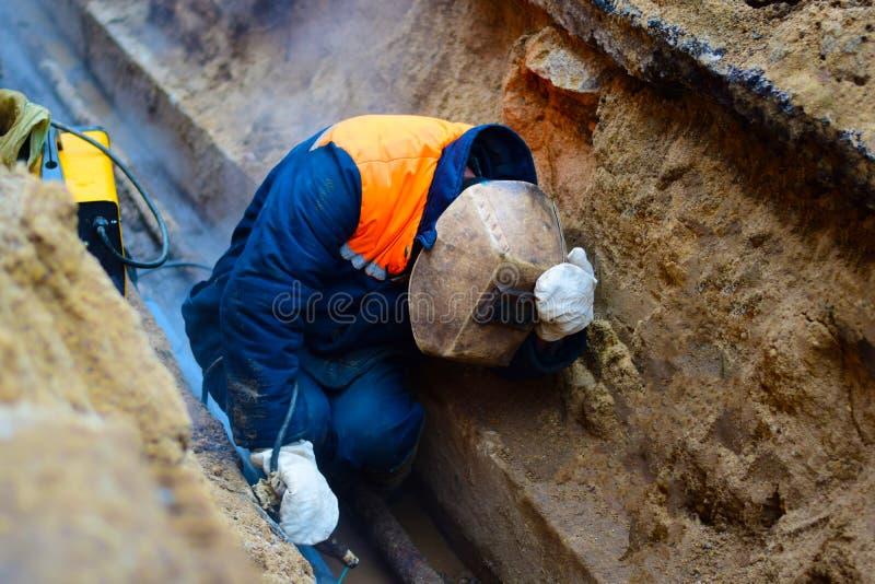 焊工在矿修理管道 免版税库存照片
