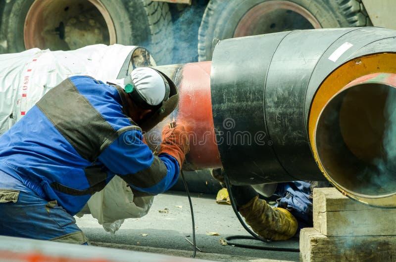 焊工焊接区城市加热系统的管子在有选择聚焦的街道上 免版税库存图片