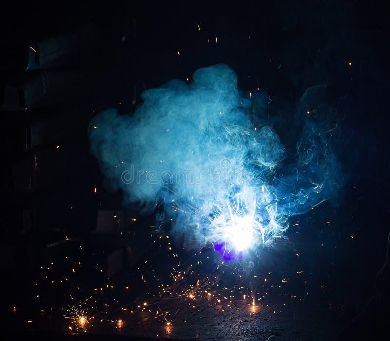 焊工焊接金属零件、许多火花和发烟,焊接,焊弧,明亮的闪光,特写镜头,焊弧 免版税库存照片