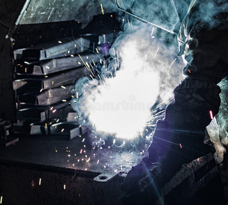 焊工焊接金属零件、许多火花和发烟,焊接,焊弧,明亮的闪光,特写镜头,焊接持有人 免版税库存照片
