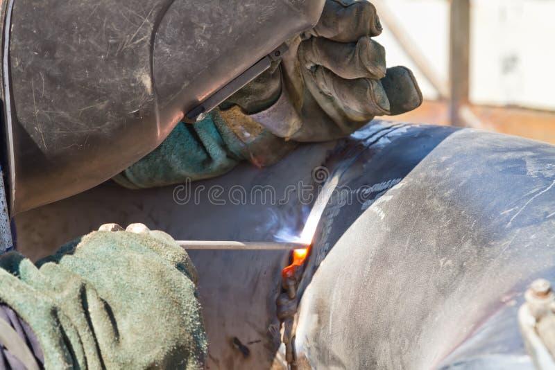 焊工进行在管道的焊接工作 免版税库存图片