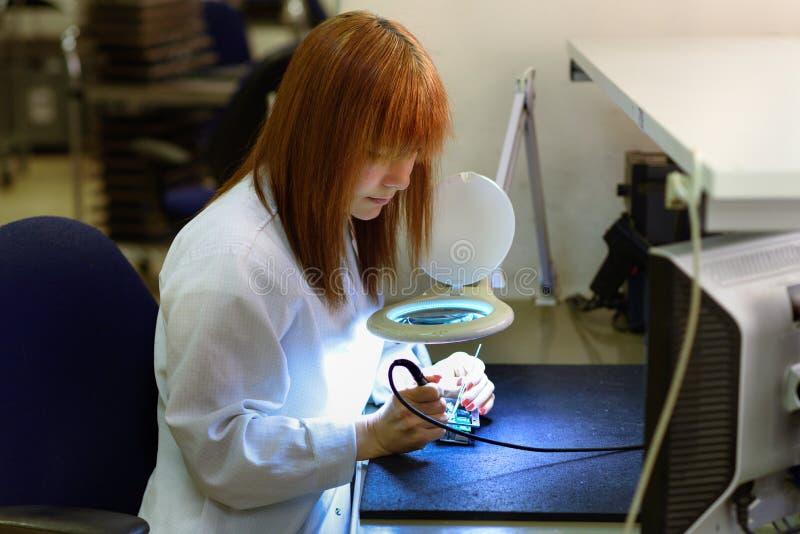焊接一张电路板的妇女在她的技术办公室 关闭女性工程师 图库摄影