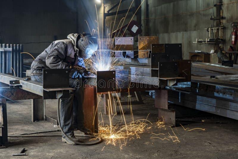 焊接与火花由过程流出的被挖出果核的电弧焊接,在工业工厂的焊工的工业钢焊工零件 库存图片