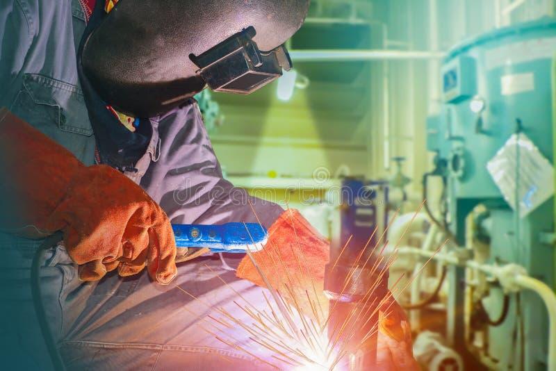 焊接在与火花光的工厂特写镜头的产业工人 库存图片