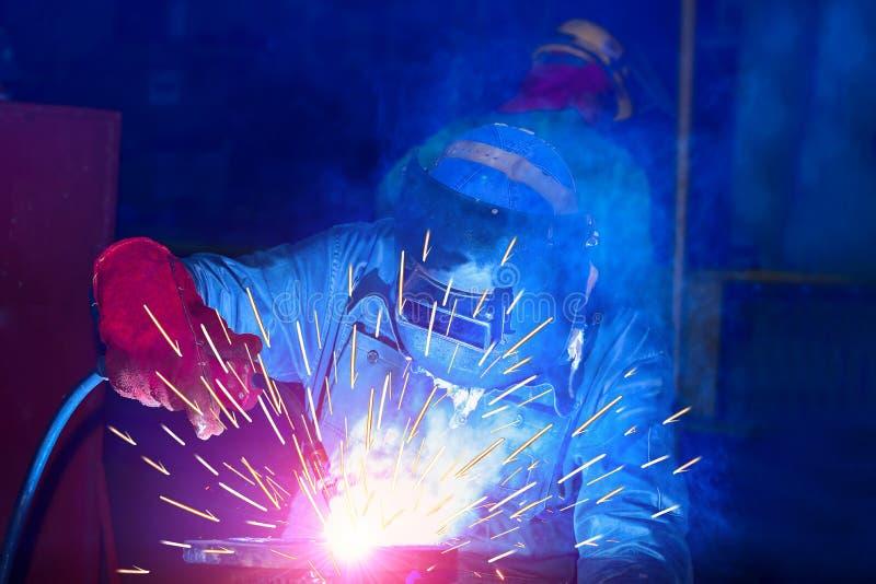 焊接在工厂的产业工人 库存照片