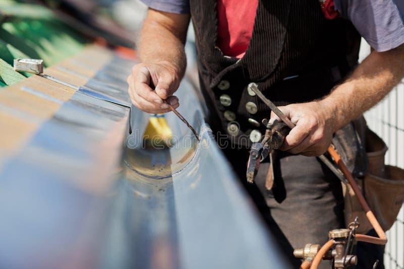 焊接天沟的盖屋顶的人的特写镜头 库存图片