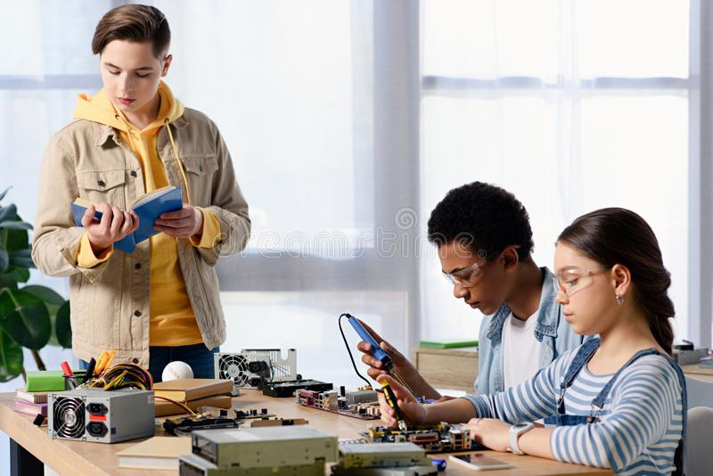 焊接有焊铁和朋友的多文化少年计算机电路 库存照片