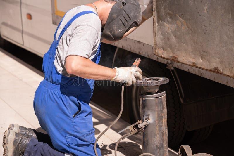 焊接的工作 总体和一个防毒面具的一名工作者焊接耳轮缘到在街道上的管子 修理工作gorodskih 库存图片
