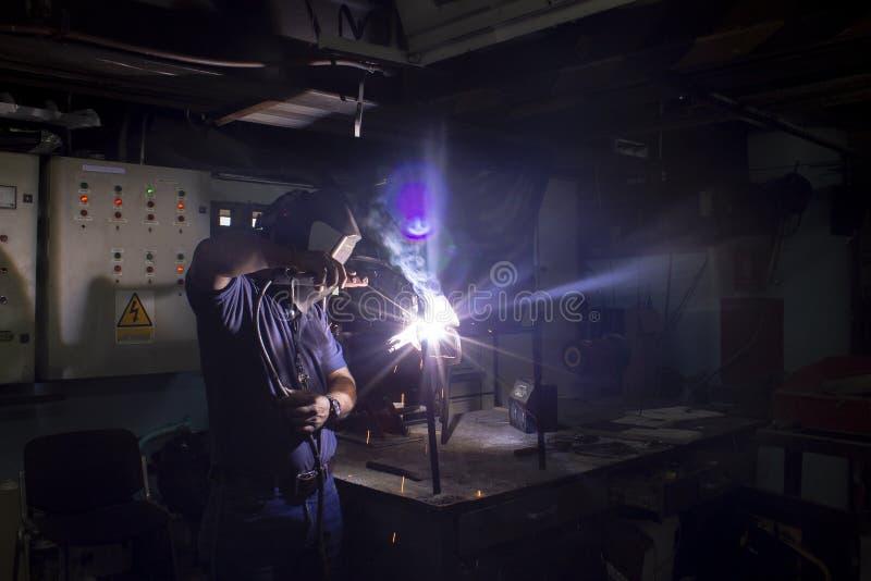 焊接的技术员,执行焊接的工作在车间 库存照片