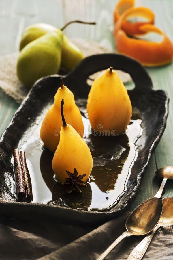 焦糖的梨-水煮的梨用在糖浆的香料在一张黑暗的木桌上的土气黏土板材 holi的可口点心 库存图片