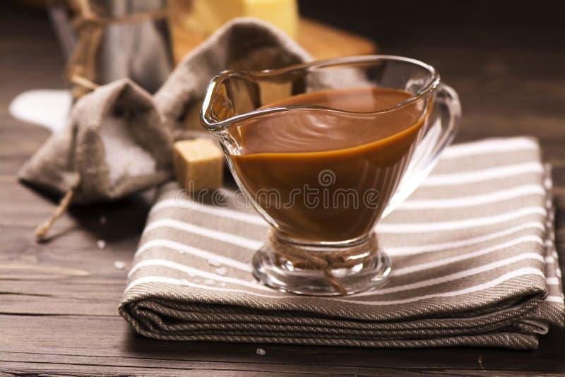 焦糖调味汁和成份在难看的东西木背景 免版税库存图片