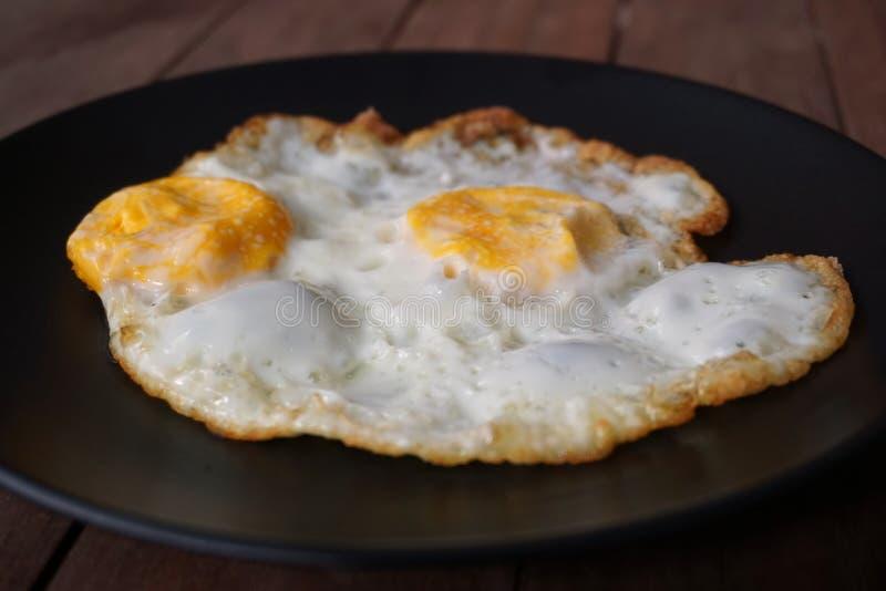 煎的黑色盘鸡蛋 库存图片
