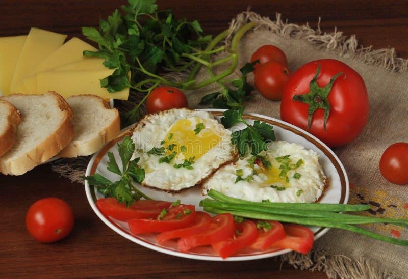 煎蛋、成熟西红柿和新鲜的草本 乳酪和白面包 免版税库存照片