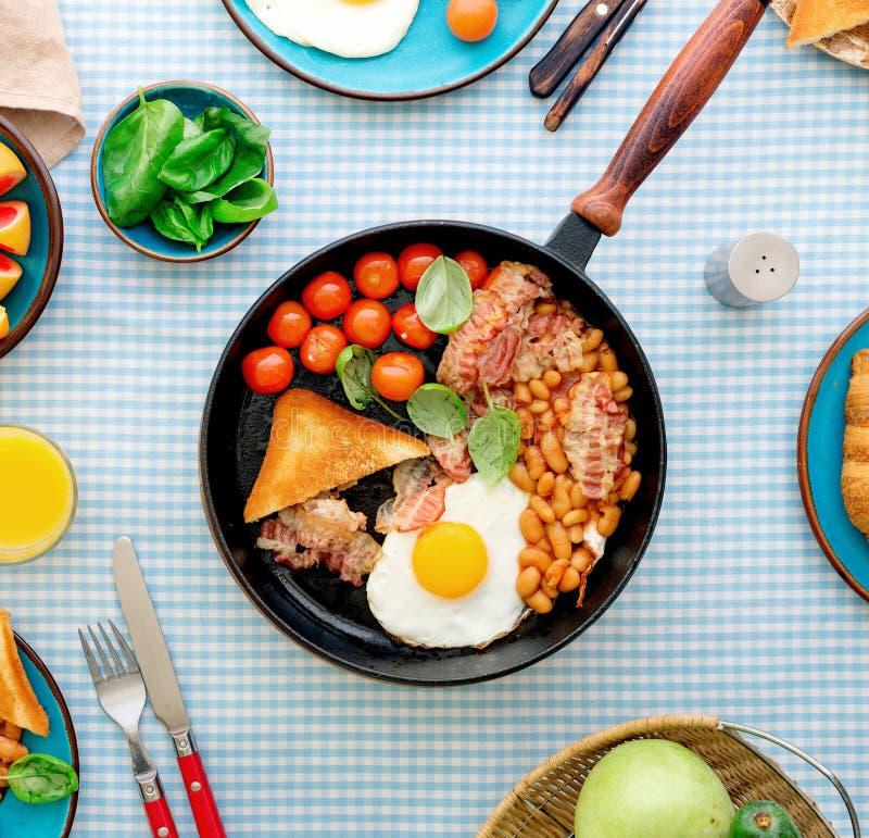 煎蛋、烟肉、蕃茄、豆和菠菜在平底锅 免版税库存图片