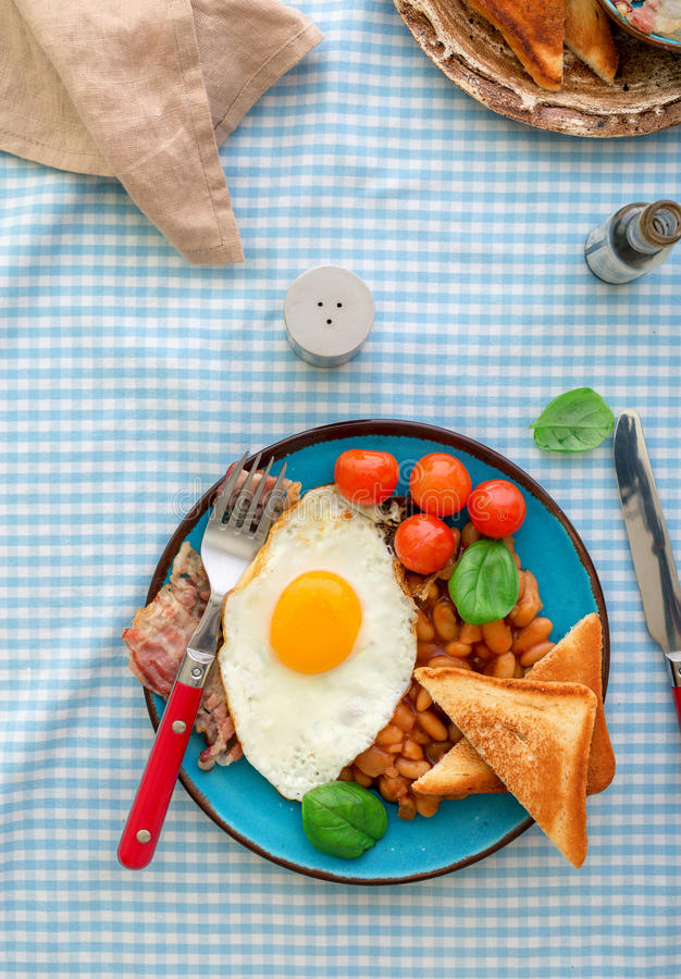 煎蛋、豆、蕃茄、烟肉和多士在板材 库存照片