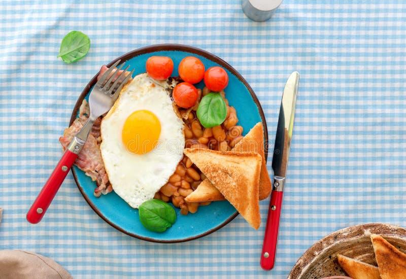 煎蛋、豆、蕃茄、烟肉和多士在板材 免版税库存图片