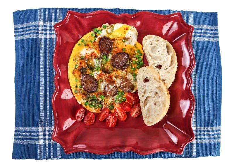 煎蛋卷用在板材和蓝色碗碟衬垫的香肠 图库摄影