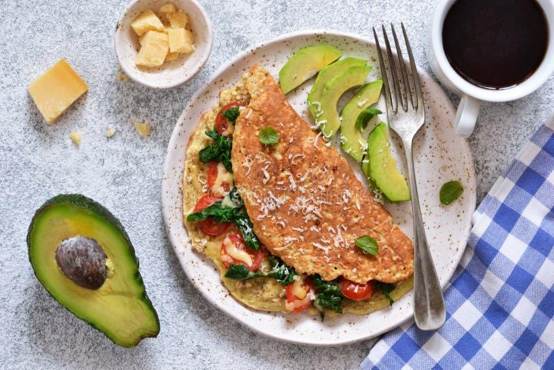 煎蛋卷用蕃茄、乳酪和蓬蒿在一块板材在厨房用桌上 o 免版税图库摄影