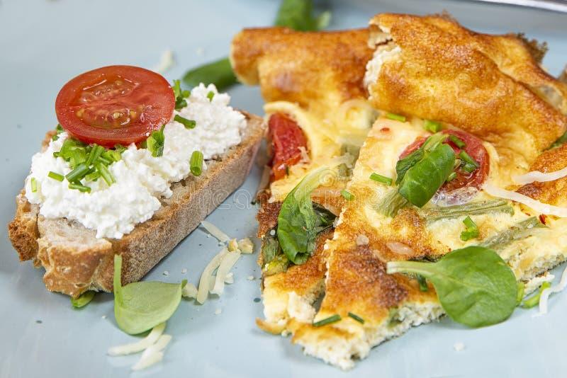 煎蛋卷被切的片断用在板材的面包 在烤箱的煎蛋卷与绿豆、蕃茄、草本和乳酪 库存图片