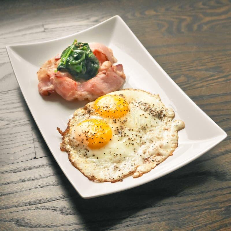 煎蛋和烟肉用菠菜 免版税图库摄影