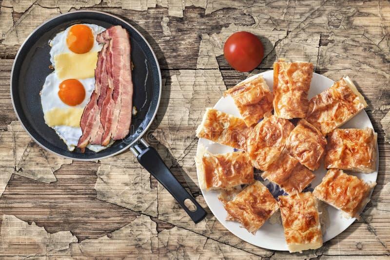 煎蛋和烟肉更卤莽在聚四氟乙烯煎锅用蕃茄和满盘Gibanica乳酪在老破裂的木头设置的饼切片 免版税库存图片
