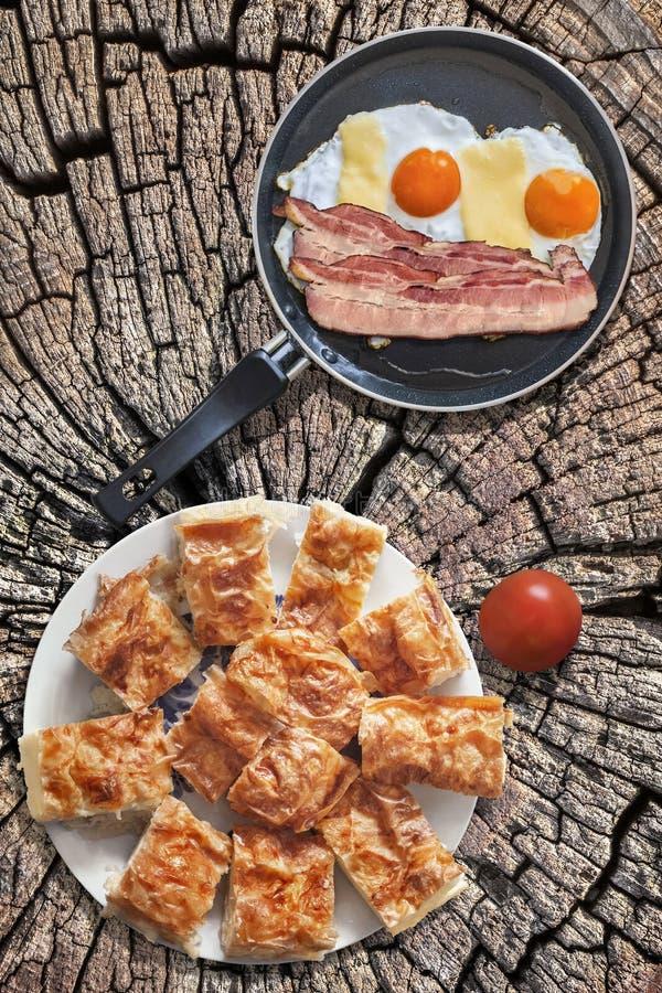 煎蛋和烟肉更卤莽在聚四氟乙烯煎锅用蕃茄和满盘Gibanica乳酪在老破裂的树桩设置的饼切片 免版税图库摄影