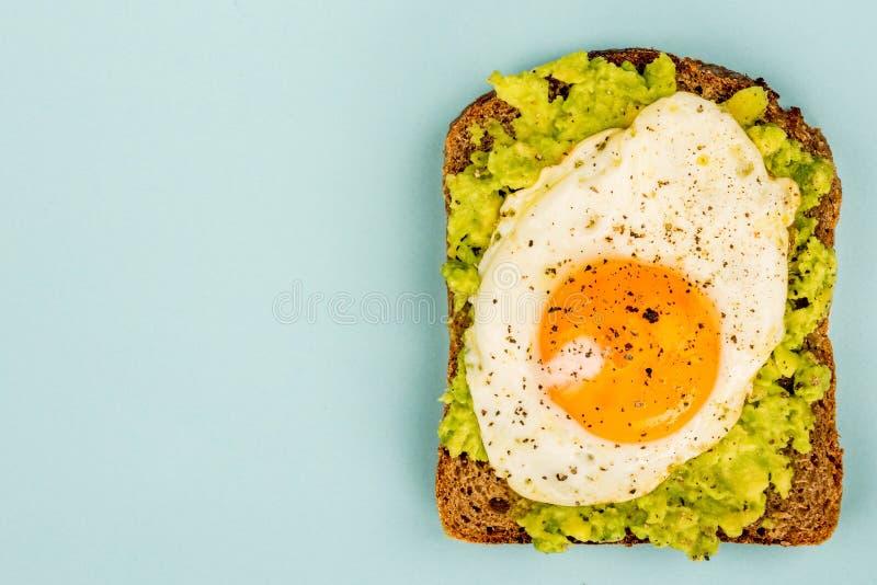 煎蛋晴朗的边在被击碎的鲕梨和黑麦面包开放Fa 库存照片