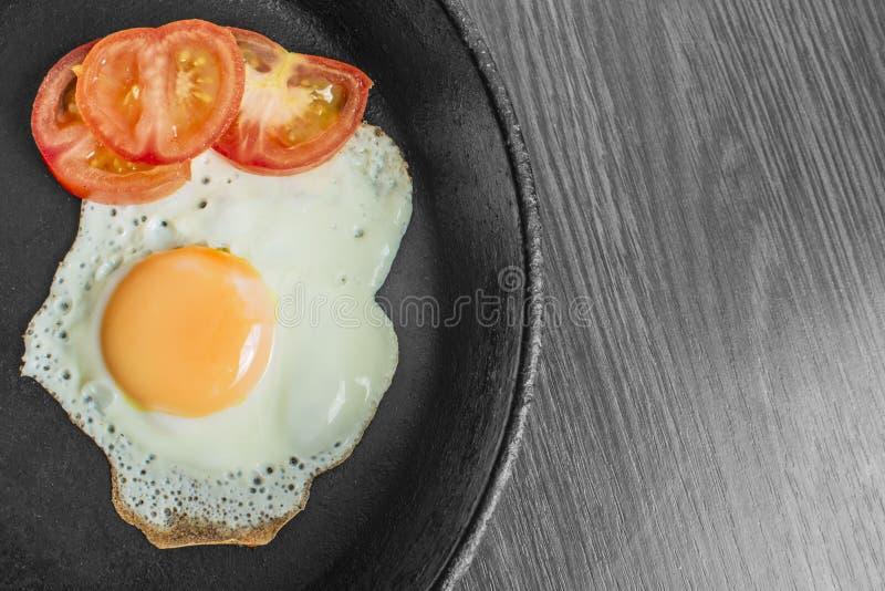 煎蛋用在铸铁煎锅的蕃茄在一张木桌上 图库摄影