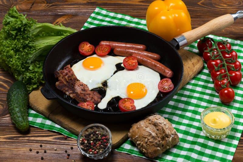 煎蛋用烟肉和香肠在煎锅 免版税图库摄影