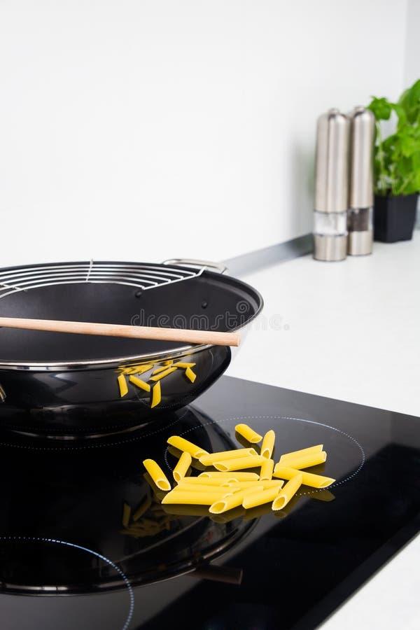 煎锅、棍子和意大利面食在现代厨房里 免版税库存照片