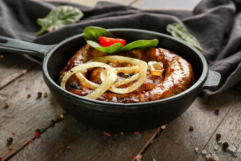 煎锅用可口烤香肠和菜在木桌上 免版税库存照片