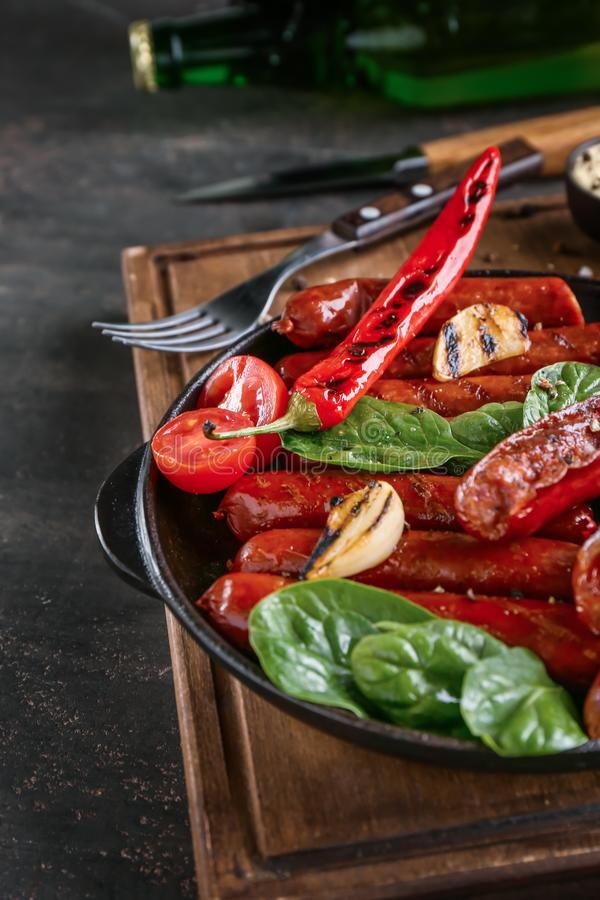 煎锅用可口烤香肠和菜在桌上 库存图片