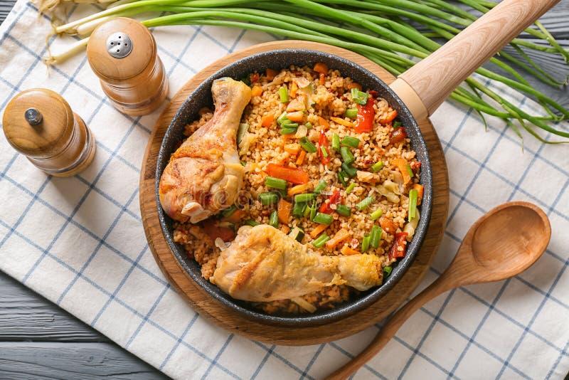 煎锅用可口煮沸的米、鸡腿和菜在木板 库存图片