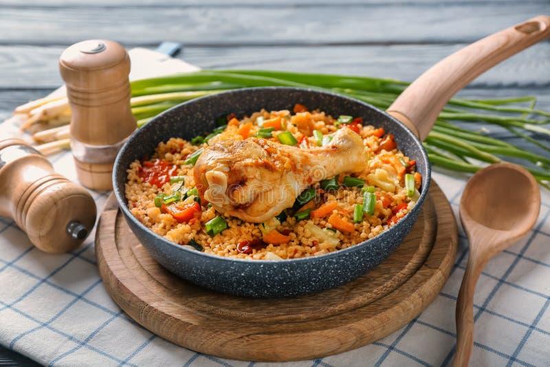 煎锅用可口煮沸的米、鸡腿和菜在木板 免版税库存图片