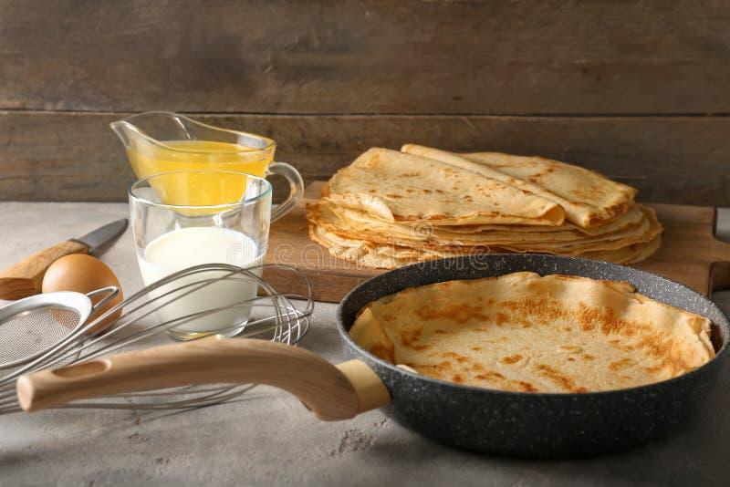 煎锅用在桌上的可口稀薄的薄煎饼 图库摄影