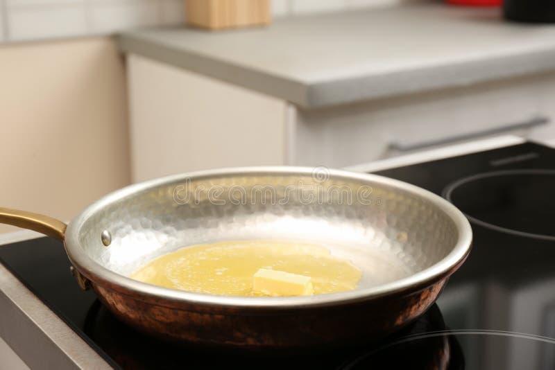 煎锅用在火炉的熔化黄油 库存图片