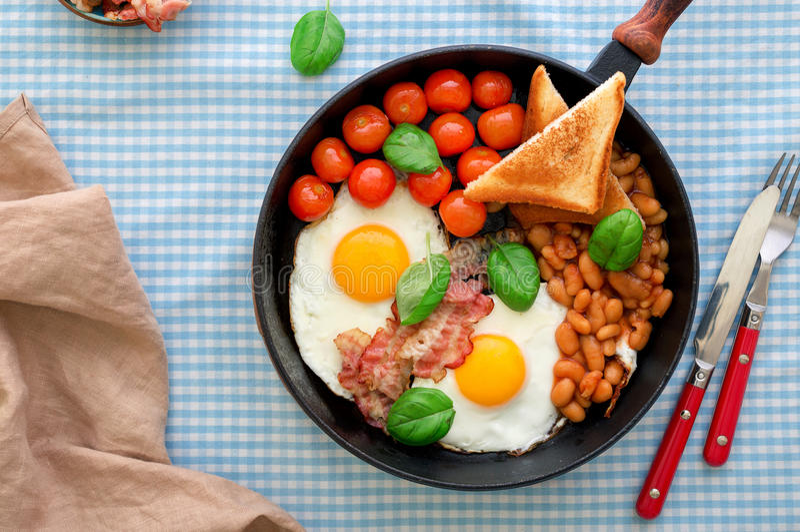 煎锅用煎蛋、豆、蕃茄、烟肉和多士 免版税库存图片