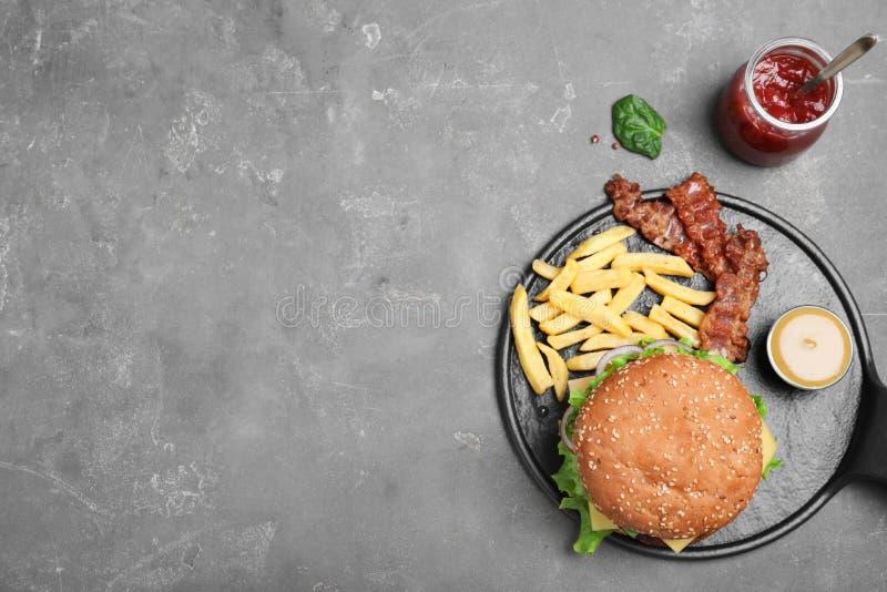 煎锅用鲜美汉堡包和薯条在灰色背景 库存图片