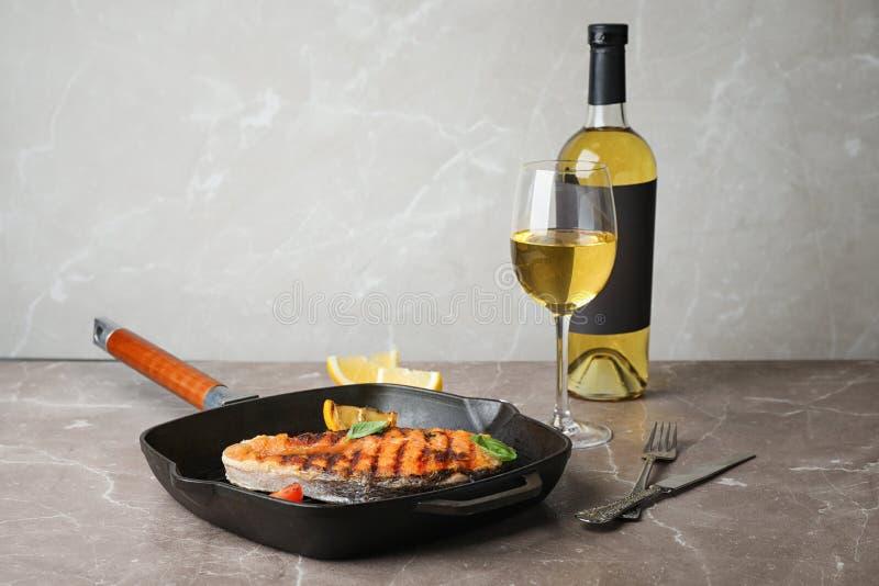 煎锅用鲜美鲑鱼排和酒 免版税库存图片