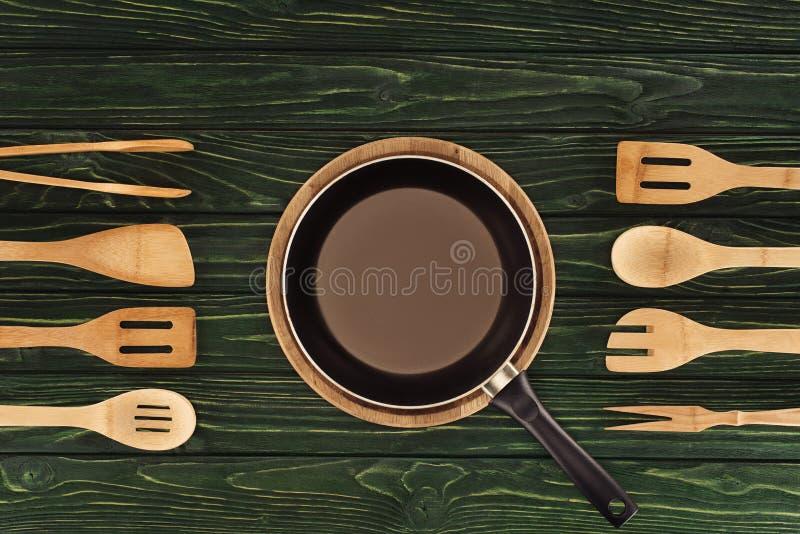 煎锅顶视图在圆的切板的在木厨房器物之间 免版税库存图片