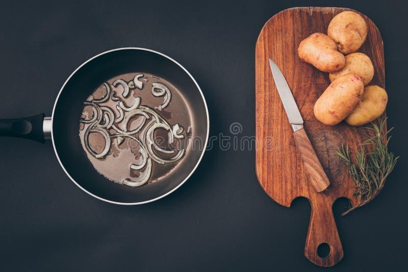 煎锅顶视图用葱和木板用土豆 图库摄影