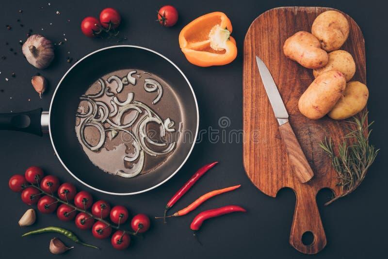 煎锅顶视图用葱和木板 图库摄影